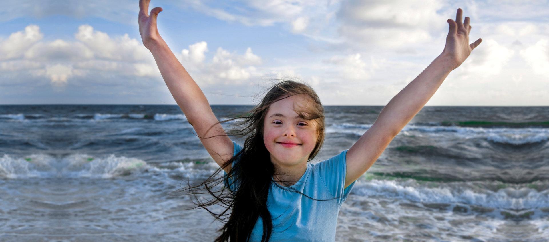 young girl raising her hands