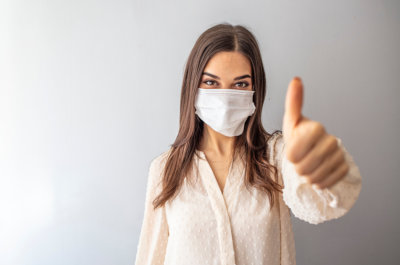 woman wearing a face mask giving thumbs up