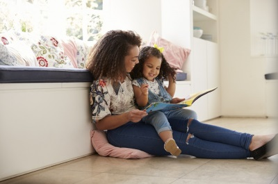 woman reading a book to a girl